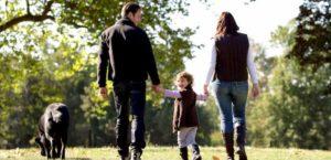 uma família com sua filha e seu cachorro preto
